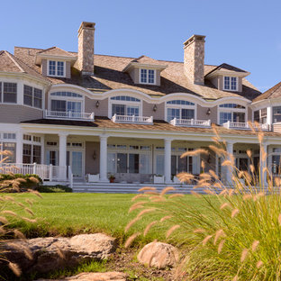 Coastal brown two-story house exterior photo in New York with a hip roof and a shingle roof