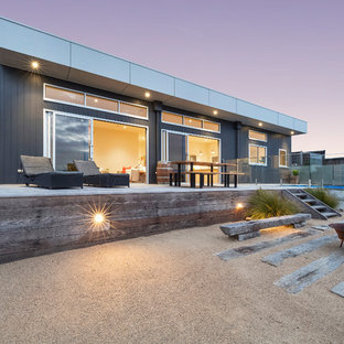 This is an example of a beach style one-storey black house exterior in Melbourne with a flat roof.