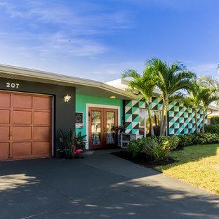 Ejemplo de fachada verde, ecléctica, de tamaño medio, de una planta, con revestimiento de estuco y tejado plano