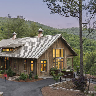 Mid-sized mountain style brown three-story wood exterior home photo in Other with a metal roof