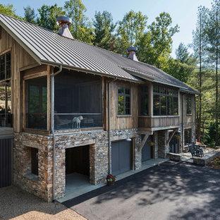 Esempio della facciata di una casa unifamiliare piccola marrone rustica a tre piani con rivestimento in legno, tetto a capanna e copertura in metallo o lamiera