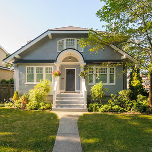 Small cottage blue two-story stucco house exterior photo in Vancouver with a clipped gable roof and a shingle roof