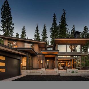 Imagen de fachada de casa marrón, rural, de dos plantas, con revestimiento de madera y tejado de un solo tendido