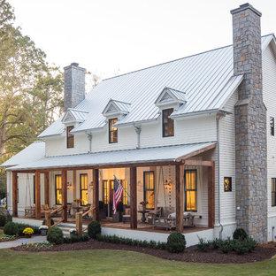 Foto della facciata di una casa unifamiliare grande bianca country a due piani con rivestimento con lastre in cemento, copertura in metallo o lamiera e tetto a capanna