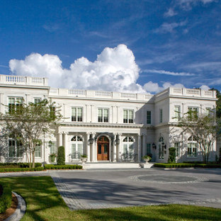 Huge traditional white two-story stone flat roof idea in Jacksonville