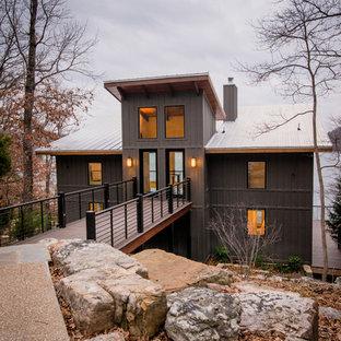 На фото: двухэтажный, серый, большой частный загородный дом в стиле рустика с односкатной крышей, облицовкой из металла и металлической крышей