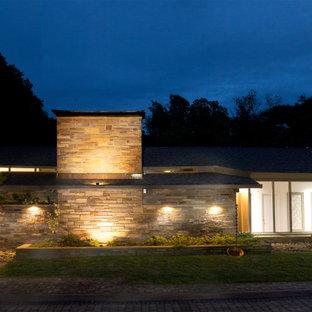 Imagen de fachada gris, retro, extra grande, de dos plantas, con revestimiento de estuco