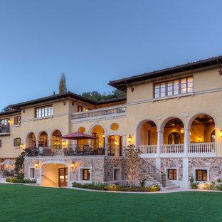 Inspiration för mycket stora medelhavsstil beige hus, med tre eller fler plan, stuckatur och platt tak