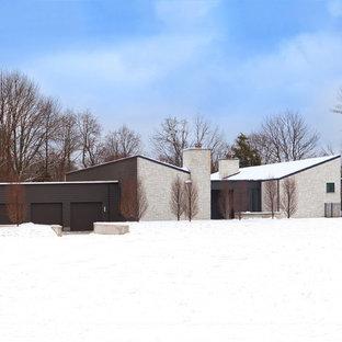 シンシナティのモダンスタイルのおしゃれな陸屋根の家 (石材サイディング) の写真
