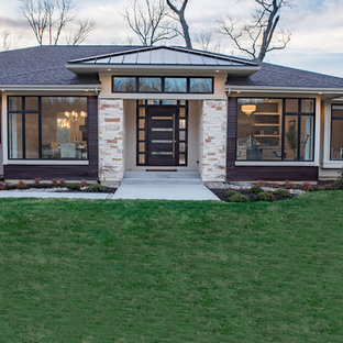 Inspiration for a mid-sized modern beige one-story stone house exterior remodel in Cincinnati with a hip roof and a mixed material roof