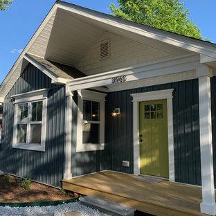 Пример оригинального дизайна: маленький, двухэтажный, синий частный загородный дом в стиле кантри с облицовкой из винила, двускатной крышей и крышей из гибкой черепицы