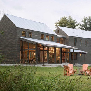 Inspiration for a large farmhouse two-story wood exterior home remodel in Portland Maine with a metal roof