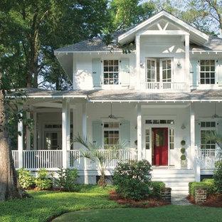 Foto della facciata di una casa unifamiliare bianca tropicale a due piani con tetto a padiglione e copertura a scandole