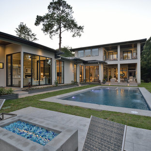Modern gray two-story stucco house exterior idea in Houston with a metal roof