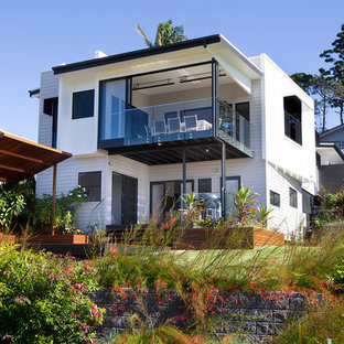 Inspiration for a contemporary two-storey white house exterior in Brisbane with a flat roof.