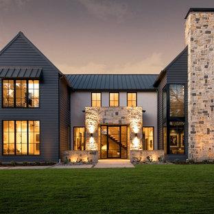 Ispirazione per la facciata di una casa unifamiliare nera country a due piani con rivestimenti misti, tetto a capanna e copertura in metallo o lamiera