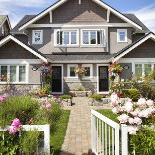 На фото: двухэтажный, серый дуплекс среднего размера в классическом стиле с двускатной крышей и облицовкой из цементной штукатурки с