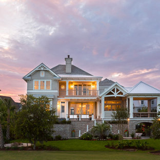 Coastal gray three-story house exterior photo in Charleston with a hip roof and a shingle roof