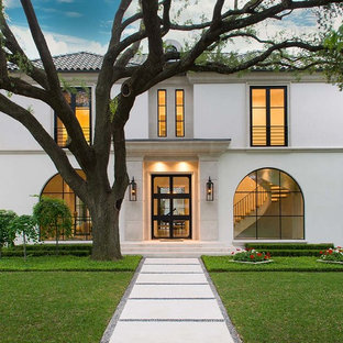 Example of a large trendy white two-story stucco house exterior design in Dallas with a hip roof and a tile roof