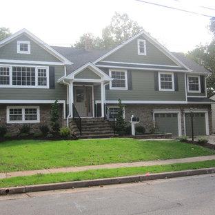 Esempio della facciata di una casa verde american style a due piani di medie dimensioni con rivestimento con lastre in cemento