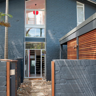 Inspiration for a mid-sized contemporary gray three-story brick gable roof remodel in Sydney