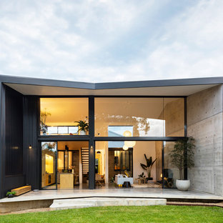 Inspiration for a modern two-storey concrete black house exterior in Sydney with a gable roof.