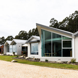 Contemporary one-storey stucco white house exterior in Hobart with a gable roof and a metal roof.