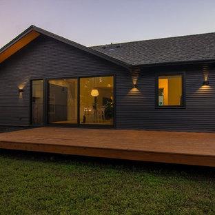 Modelo de fachada de casa negra, escandinava, pequeña, de una planta, con revestimiento de madera, tejado a dos aguas y tejado de teja de madera