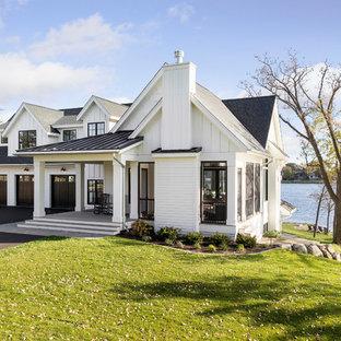 Modelo de fachada de casa blanca, marinera, de dos plantas, con tejado a dos aguas y tejado de varios materiales