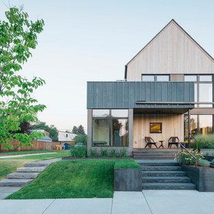 Immagine della facciata di una casa unifamiliare piccola beige contemporanea a due piani con rivestimento in legno e tetto a capanna