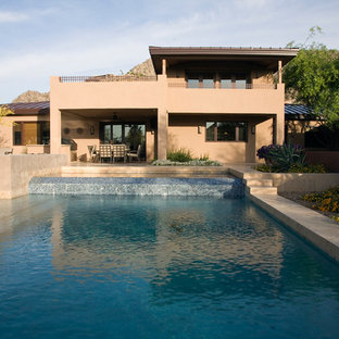 Inspiration for a mid-sized southwestern beige two-story stucco flat roof remodel in Phoenix