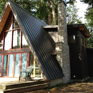 Example of a mid-sized mountain style black two-story wood exterior home design in Seattle