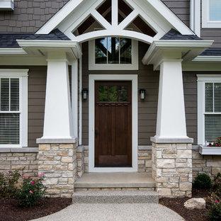 Imagen de fachada marrón, de estilo americano, grande, de dos plantas, con revestimiento de aglomerado de cemento