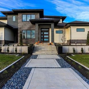 Ejemplo de fachada beige, actual, de dos plantas, con revestimientos combinados y tejado a cuatro aguas