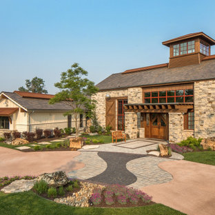 Inspiration for a cottage beige one-story stone exterior home remodel in Omaha with a shingle roof