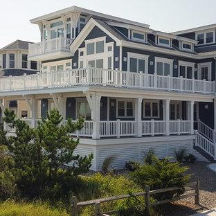 Modelo de fachada de casa azul, marinera, grande, de tres plantas, con revestimiento de vinilo, tejado a dos aguas y tejado de teja de madera