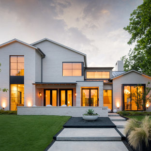Foto della facciata di una casa unifamiliare grande bianca contemporanea a due piani con rivestimento in pietra, tetto a capanna e copertura in metallo o lamiera