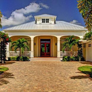 Idee per la facciata di una casa unifamiliare gialla tropicale a un piano di medie dimensioni con rivestimento in legno, tetto a padiglione e copertura in metallo o lamiera