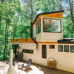Modelo de fachada blanca, de estilo de casa de campo, de dos plantas, con revestimiento de metal y tejado de un solo tendido