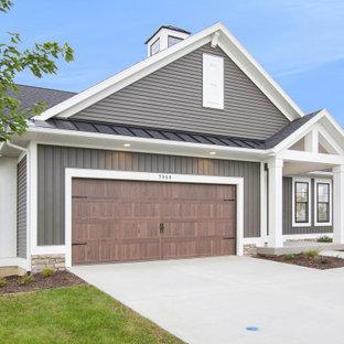 Идея дизайна: одноэтажный, серый многоквартирный дом в стиле кантри с облицовкой из винила, двускатной крышей и крышей из смешанных материалов