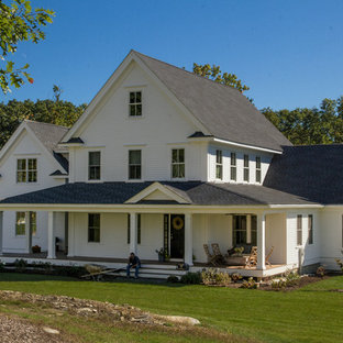 Example of a large farmhouse white two-story adobe exterior home design in Boston with a shingle roof