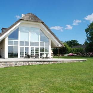 Foto de fachada blanca, de estilo de casa de campo, grande, con revestimiento de vidrio y tejado de un solo tendido
