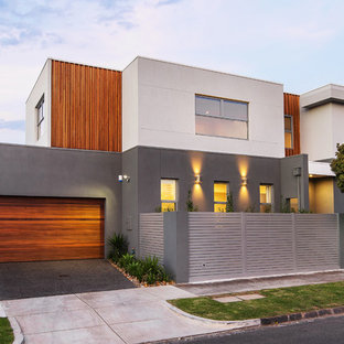 Design ideas for a contemporary two-storey exterior in Melbourne with mixed siding and a flat roof.