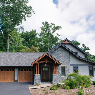 Mid-sized rustic gray three-story concrete fiberboard gable roof idea in Other