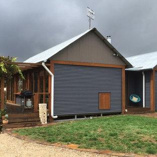 Foto de fachada de casa gris, bohemia, grande, de una planta, con revestimiento de metal, tejado de metal y tejado a dos aguas
