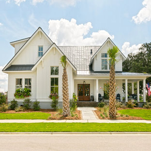 Coastal white two-story exterior home photo in Charleston with a metal roof