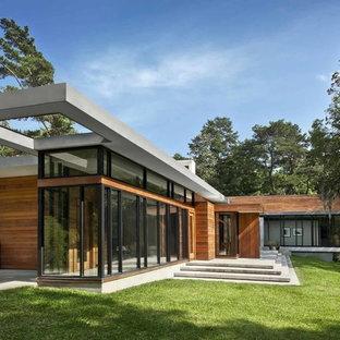 Idee per la facciata di una casa grande moderna a un piano con rivestimento in legno e tetto piano