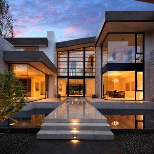 Exempel på ett stort modernt beige hus, med två våningar och glasfasad