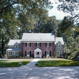 Large elegant red two-story brick exterior home photo in New York with a shingle roof