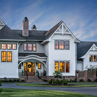 Foto de fachada de casa blanca, tradicional, grande, de dos plantas, con revestimiento de madera y tejado de varios materiales